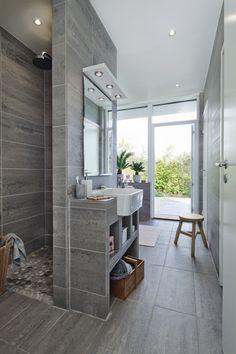 Badrummet är klätt med stora plattor i granitkeramik – effekten blir harmonisk med lite rå känsla. Här rymms både dusch och badkar.