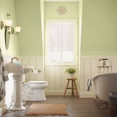 PAIR A SOFT NEUTRAL COLOR WITH A WALL TREATMENT-  In the photo, the bathroom features a creamy white wainscoting on the bottom of the wall, paired with a soft green on the top. By balancing texture and color, you're left with a charming, neutral space that is anything but dull.