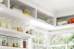 """A step stool makes accessing ceiling-high storage easy. The """"pocket"""" shelves were deliberately left open so that Jill wouldn't forget about her trove of cookbooks and serving pieces. Paint (walls and upper cabinets): Frazee Paint's Akamina"""