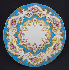 Wonderful ~ Antique ~ Cauldon English Cabinet Plate ~ It is made of fine white bone china ~ The plate has borders of vibrant turquoise enamel ~ There are 6 cartouches with elaborate raised gilding near the border of the plate ~ Sprays of colorful hand painted flowers are contained in these reserves ~ The flowers are realistic and they are all different ~ Near the cnter of the plate is another row of decorations with raised gilding ~ Produced in England by Cauldon ~ Circa around 1900