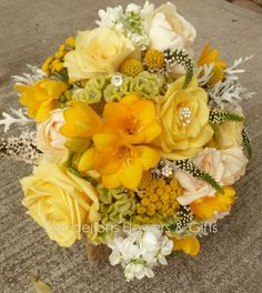 Shades of yellow | roses, freesia, cockscomb, Veronica, button yarrow, craspedia, and dusty miller