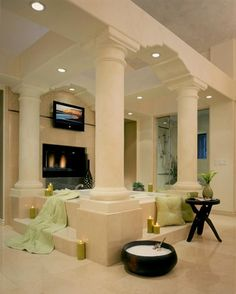 This ultra-luxurious bathroom is dominated by the soaking tub at center, surrounded by four large stone pillars. The fireplace is mounted in the wall above the tub, while rich tile spreads in every direction.