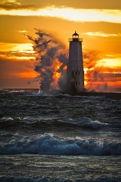 Wave crashing on a lighthouse at sunset