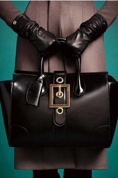 Black leather bag with huge buckle and black gloves