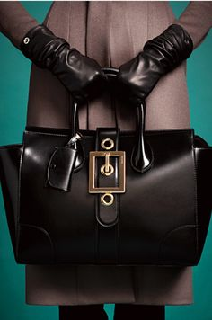 Black leather bag with huge buckle and black gloves