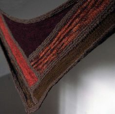 With long, sweeping lines that intersect in a bold central motif, this unusual scarf's best feature is the showcase it provides for hand-spun yarns with rich color and texture. Its unique construction, inspired by quilting, starts with a central triangle worked side to side. You then pick up stitches along the sides of the triangle, and build the shawl outwards in the same way that a quilter adds sequential strips of fabric to make a log cabin quilt block.