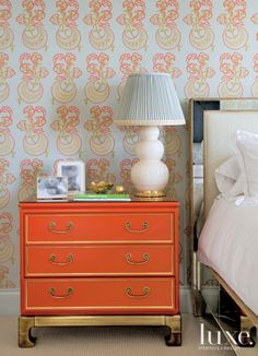 Katie Ridder's Moon Flower wallpaper brings out the bright color notes seen in this coral Mastercraft nightstand.
