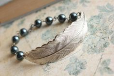This is a beautiful silver brass feather bracelet with linking swarovski pearl beads in gorgeous smokey midnight blues! Woodland and nature