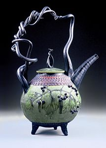Basket Handled Teapot by Suzanne Crane. Wheel-thrown and handbuilt stoneware teapot decorated with a hand-pressed scale pattern. Green copper-ash glaze with black trim and red iron oxide detailing.