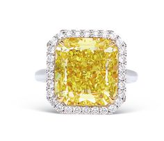 The cut-cornered rectangular-shaped fancy vivid yellow diamond, weighing approximately 12.88 carats, to brilliant-cut diamond surround, mounted in 18k white gold, ring size 6 1/2. Accompanied by the report no.2105471984 dated 23 December, 2008 from GIA stating that the 12.88 carat diamond is fancy vivid yellow, natural colour, VS2 clarity.