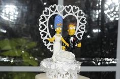 "Hom/Eastwood Wedding (4): About the only thing they splurged on was a Marge and Homer Simpson cake topper.  ""I didn't want our cake to be just some boring cake,"" Elaine says. ""I wanted something with a touch of humor that would also be meaningful to us, and the Simpsons are the best representation of a couple that I can think of.  ""It's funny that the cake topper ended up being more expensive than Brian's suit."""