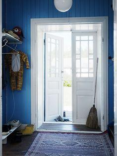 Mattan i den blåmålade hallen kommer från Pinemont Trading. Den röda hunden på hatthyllan är från Acne Junior.
