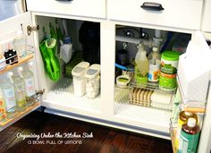 Get Hooked By simply installing adhesive hooks, you can transform the quagmire of clutter under the sink into an organizational oasis. Here, hooks mounted to the sides of the cabinet carry lightweight gloves and scrubbing brushes, while accompanying shelves shelter household cleaners and wipes.