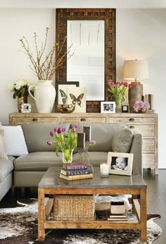 A large reclaimed console and faux cowhide rug diversify the nuanced neutrals of this room. #rustic #sofamart #oakexpress