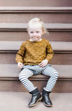 Hipster baby girl style from Noble Carriage by Hansel from Basel. Street style urban babe sitting out on the stairs in the crisp cool autumn air. Cute little boho outfit with pompom knit sweater in nutmeg by Misha + Puff from Noble Carriage. Made from Alpaca so it'a warm and cozy, and sustainably made cruelty-free and fair-trade. Holiday wish list is so full with Noble Carriage curated organic baby gifts!
