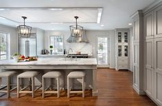 White and gray kitchen features a white ceiling framed with glossy gray beveled trim accented with a pair of Darlana Medium Lanterns illuminating a light gray center island topped with calacatta marble fitted with a sink and deck mount faucet lined with backless gray upholstered bar stools.