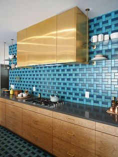 Dreamy modern kitchen with a nod to mid century design. Turquoise subway tiles & a brass oven hood