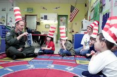 "An Air Force Colonel reads ""The Cat in the Hat"" to a group of elementary school students for Read Across America Day."