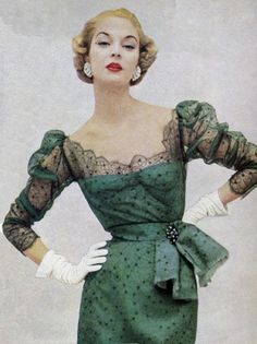 Jean Patchett in a green cocktail dress with black lace overlay, 1950s.