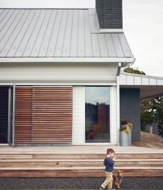 Link Catlett and Butters, the dog, stroll alongside their home's namesake wraparound porch, made of Brazilian ipe. Rolling slatted doors ...