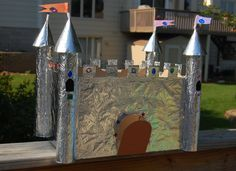 Castle, made out of a packing box. The turrets/towers are the inner tubes of paper towels topped with cardboard cones. The entire thing is covered with aluminum foil except for the drawbridge, its decorated it with adhesive jewels and stuck in the flags.