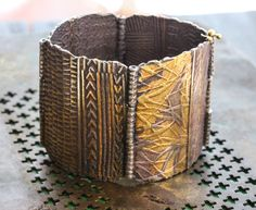 This bracelet has been in many magazines and won awards for design. Its made by collaging ancient scripts into textures and each panel is textured on