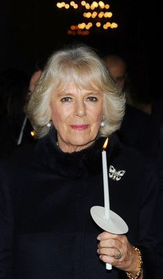 Camilla holding a lit candle at the Maggie's Christmas Carol concert at St Paul's Cathedral on December 16th.