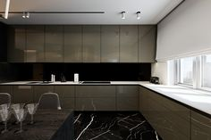 Glossy cabinetry features a hue somewhere between coffee and brass, drawing extra attention to the clean white worktops. The backsplash looks jet-black from this perspective yet matches the tone of the cabinets as seen from the other angles – a neat optical illusion that increases perceived depth.