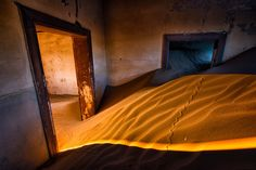 Interior photo of a sand filled room in the abandoned mining town of kolmanskop