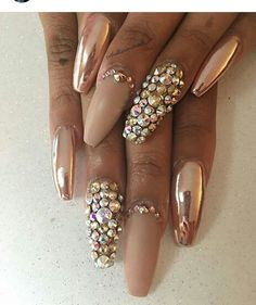 Nude nails accented with rose gold chrome and gold jewels and studs