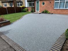 A resin driveway with black block edging laid sideways creates a really dramatic driveway for this home in South London. Resin Driveway, Gravel Driveway, Driveway Landscaping, Front Garden Ideas Driveway, Driveway Design, Garden Wall Planter, Wall Planters, Driveway Apron, Resin Bound Driveways