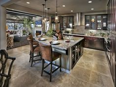 A fan shaped island with open shelves,  glass front cabinets flank a stainless steel range hood. The Villa Brisas del Mar plan by Ryland Homes in San Marcos, CA.