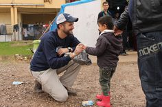 Isaac Eagan, an Iraq combat veteran, trades smiles with a little boy in one of the refugee camps after getting him set up with a new pair of rubber boots.  #ISIS #refugees #Iraq #Kurdistan #SpiritofAmerica #SoA #humanitarian #children #Erbil #boots #nonprofit #winter