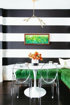 bold black & white stripes painted in the dining area; emerald green tufted banquette; louis ghost chairs, saarinen pedestal table