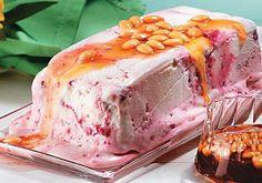 Sobremesa de sorvete de iogurte com frutas vermelhas e calda de amêndoa.