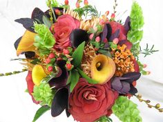 Bridal bouquet with roses, mini callas, hypericum berries, spider mums, Bells of Ireland, eucalyptus, wax flower, bay laurel, rosemary, seed pods