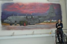 Air Force Senior Airman Patrick Corcoran stands in front of a mural he airbrushed at Davis-Monthan Air Force Base, Ariz., Oct. 17, 2013. The mural took him about six weeks to complete and is the second of five murals to be painted in the 755th Aircraft Maintenance Squadron hangar. U.S. Air Force photo by Airman 1st Class Betty R. Chevalier