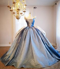 Vintage inspired Cinderella ball gown has silver brocade bustle on both side that is attached to the corset top. The top is embellished with
