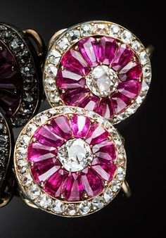 A pair of antique ruby diamond and gold set cluster earrings, probably British or American, 19th century. Each domed earring with a solitaire old European cut diamond surrounded by modified tapering emerald cut rubies to an outer border of small old cut diamonds in 18ct. yellow gold. #antique #earrings