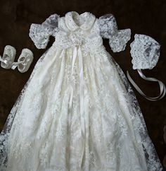 If you desire the best for your dear one, then look no further. You have come to the right place and we are glad that you have done your research well. Please do checkout our customer feedback reviews. GOWN DESCRIPTION: - Off White Christening Gown with bonnet and shoes - Exquisite Lace Overlay with Satin Underlay - Bell Sleeves sleeves - Dress length: 42 inches - Lace Bow at the waist - Hand sewn pearls on the skirt scallop, bodice, sleeves, bonnet and booties - All the photos in the…