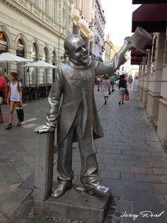 la statue de Schone Naci, il est connu comme étant une légende de Bratislava. Il était également une figure connue du 20ème siècle. Un homme pauvre et handicapé mentalement, il paradait dans les rues de la ville dans un ensemble vieux mais toujours élégant – une redingote de velours, et saluant les passants avec son chapeau haut de forme et s'inclinant avec courtoisie devant les femmes qu'il croisait.