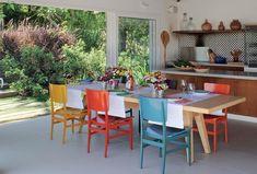 A área gourmet fica integrada ao jardim por meio da grande abertura, fechada por portas de correr. a disposição dos móveis permite o uso da área para diferentes ocasiões. As cadeiras de madeira pintada, da Etel, descontraem a mesa de almoço. Guardanapos e (Foto: Casa e Jardim)