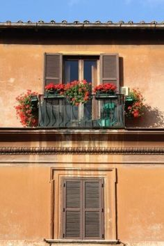 Rome, Italy. Beautiful window decorated with red flowers. Stock Photo