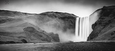 Strangers in Awe - A black and white, long exposure, landscape image of two strangers standing in awe in front of Skógafoss in Southern Iceland.   I have been working on this image for quite some time now, returning to it from day to day. I think I am finally happy with this completed edit. I don't normally do black and white landscape images but I really think this one benefits from that treatment. I hope you all like it too. :-)