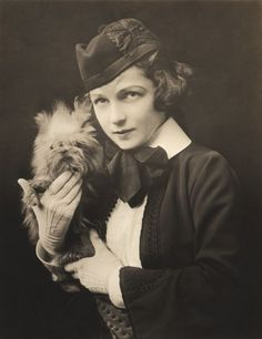 Irene Castle in Scottish Highland Costume Holding a Griffon ca. 1910   Irene Castle was born Irene Foote in 1893 in New Rochelle, New York. Irene was a debutante and actor after the turn of the century when she met Vernon Blythe (later Vernon Castle), a British actor and magician. They married in 1911 and moved to Paris after a job offer. Later in Paris, they performed at a famous café at the request of some distinguished guests, and Irene and Vernon Castle made such an impression that…