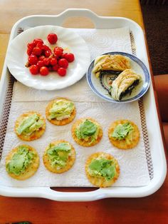 Light lunch of avocado and feta on water cracker with cherry tomatoes sautéed with olive oil and garlic and homemade spinach and feta filo