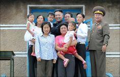 GOD STEMNING: Bortsett fra mannen i uniform til høyre i bildet, ser det ikke ut som denne familien satte stor pris på å få ta bilde sammen med landets diktator og største superstjerne, Kim Jong-un. Foto: Reuters