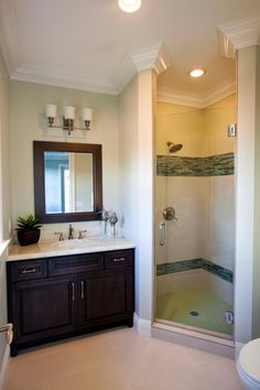 This simple guest bathroom features a walk-in shower and dark brown vanity. To give the space a custom look, bands of green glass tiles are used in the shower and a creamy onyx countertop sits on the vanity.