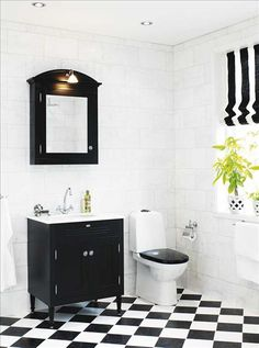 black and white bathroom. Like the angled tiles and the lack lid n the toilet.