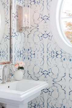 Lindsay Cowles Wallpaper line the walls of a blue powder room accented with a polished nickel mirror and a white pedestal sink fitted with a polished nickel gooseneck faucet lit by an Aerin Deauville Single Sconce.